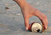 Photo of a person's hand picking up an empty aluminum can.